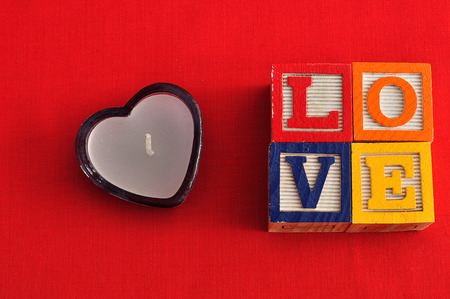 Valentines Day.Love Spelled with colorful alphabet blocks and a heart shape candle Stock Photo