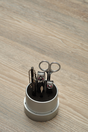 manicure set: A manicure set or tools in a container on a wooden background Stock Photo