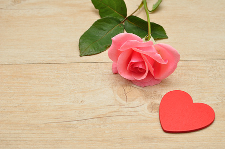 Valentines Day. A pink rose and a red heart Stock Photo