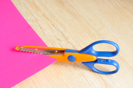 illustrating: A colorful scissor that cut a zigzag pattern with a pink paper illustrating the pattern Stock Photo