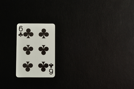 clovers: Playing card. Six of clovers isolated on a black background