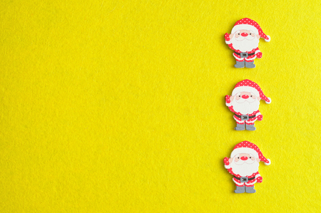 Row of Santa clauses isolated on a yellow background