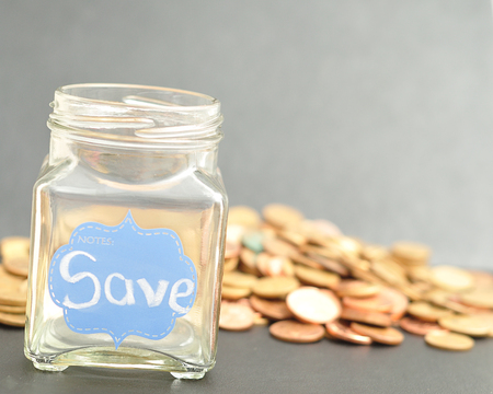 empty jar: An empty jar with the word save on it and coins that is out of focus Stock Photo
