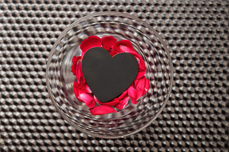Valentines day. A glass filled with dead rose petals and a little black heart displayed against a  black background