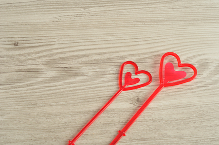 holding notes: Valentines Day. Red hearts for holding notes in a flower arrangement isolated against a wooden background