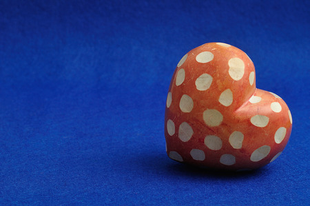 Valentines day. A spotted red and white heart isolated on a blue background