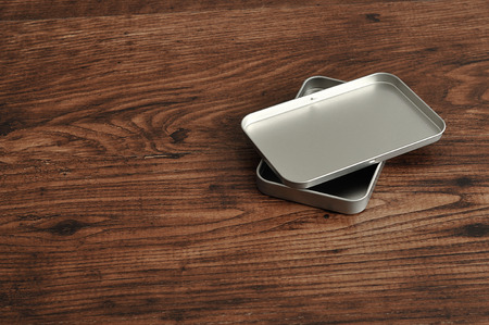 lid: A small empty metal tin with a lid