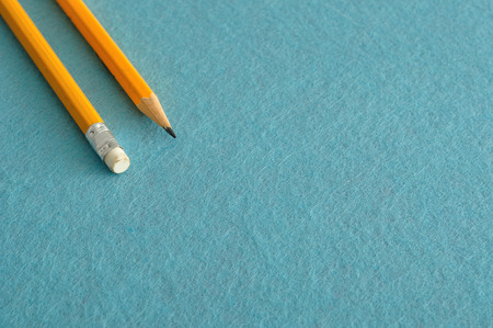 Two writing pencils, one sharpened and the other ones back end with the eraser, isolated on a blue background