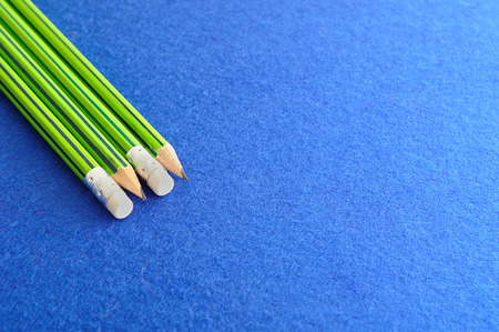 Writing pencils with erasers at the tip isolated on a blue background