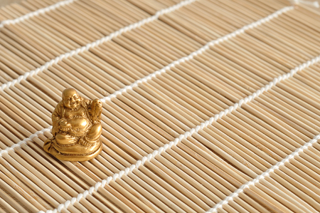 Figurine of a laughing and cheerful golden Buddha isolated on a bamboo background