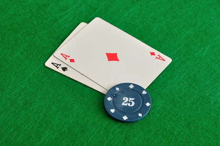 Two cards with poker chips on a green background Stock Photo