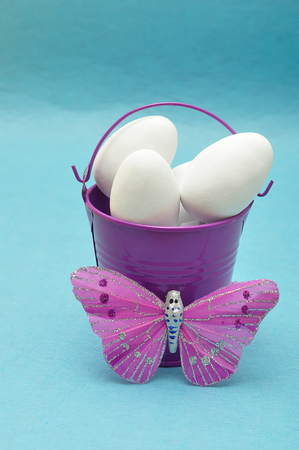 purple metal: A purple metal bucket filled with white easter eggs displayed with a silk butterfly against a blue background Stock Photo