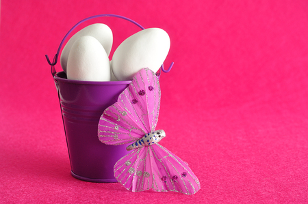 purple metal: A purple metal bucket filled with white easter eggs displayed with a silk butterfly against a pink background