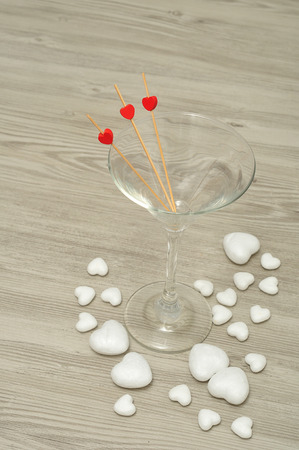 polystyrene: Valentines day. A martini glass with three sticks decorated with red hearts and polystyrene hearts Stock Photo