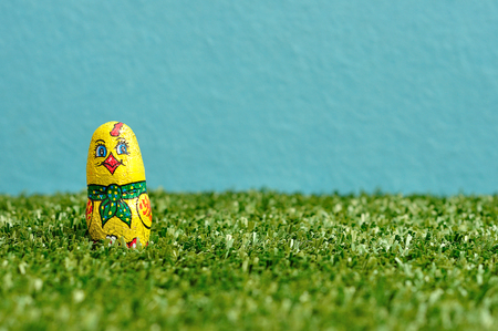 An easter chick displayed on artificial grass and a blue background