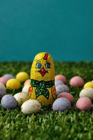 An easter chicken displayed with speckled easter eggs