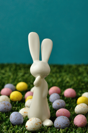 A white plastic bunny figurine displayed with speckled easter eggs Stock Photo