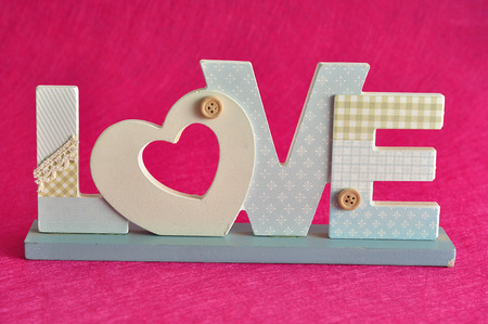 Valentines Day. Love in blue letters isolated on a pink background Stock Photo