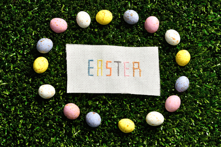 Easter cross stitched on textile isolated on artificial grass displayed with speckled eggs Stock Photo
