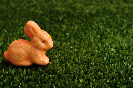 An orange bunny for easter decoration displayed on artificial grass