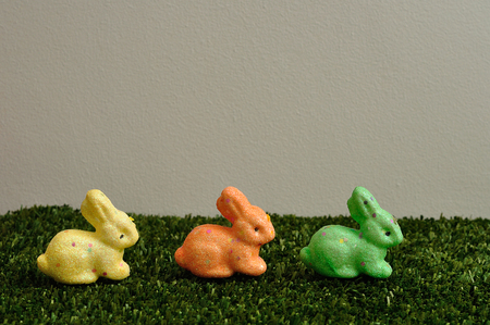 A row of colorful bunnies for easter decoration displayed on artificial grass