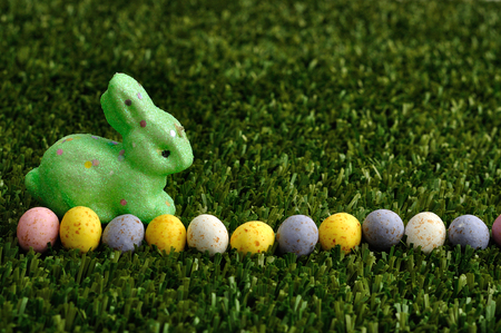 A green bunny with a row of speckled easter eggs