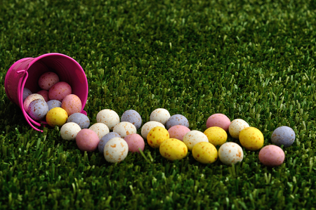Small speckled easter eggs spilling out of a pink bucket unto artificial grass Stock Photo