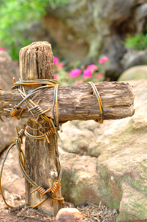 A wooden cross wrapped in barb wire in a garden for easter