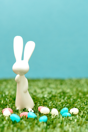 A white plastic bunny figurine displayed with jelly beans