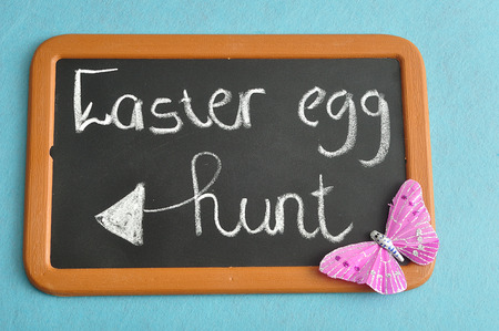 A blackboard with the words easter egg hunt with a pink butterfly Stock Photo