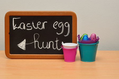 A blackboard with the words easter egg hunt with buckets and colorful easter eggs