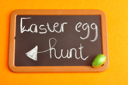 A blackboard with the words easter egg hunt and a green easter egg Stock Photo