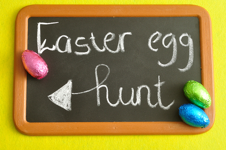 A blackboard with the words easter egg hunt and colorful easter eggs