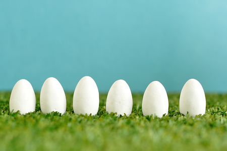 A row of white easter eggs displayed on artificial grass