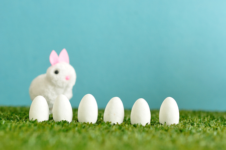 A row of white easter eggs with a fluffy bunny that is out of focus Stock Photo