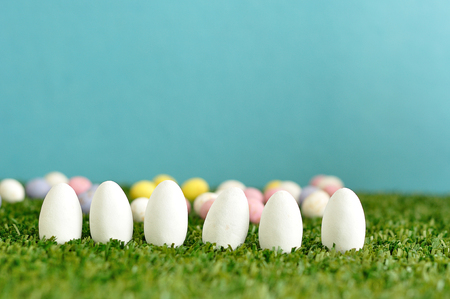 A row of white easter eggs displayed on artificial grass with speckled easter eggs that is out of focus Stock Photo