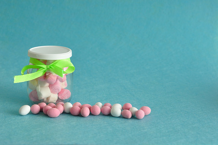 A jar filled with marshmallows and displayed with candy