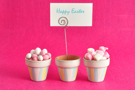 Little containers filled with white and pink candy and a happy easter card Stock Photo