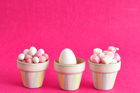 Little containers filled with white and pink candy and a white easter egg