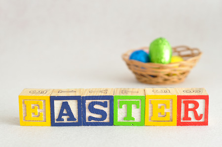 Easter in alphabet blocks with easter eggs in a basket that is out of focus Stock Photo