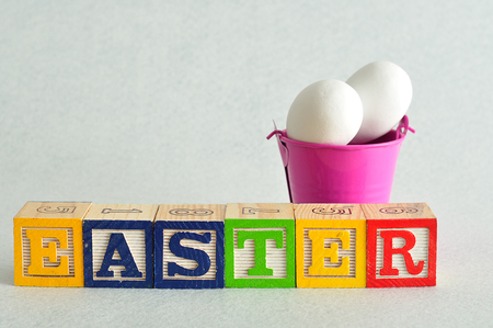 spelled: Easter spelled with alphabet blocks and a bucket of white easter eggs