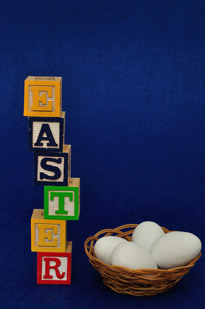 Easter spelled with alphabet blocks and a basket of white easter eggs