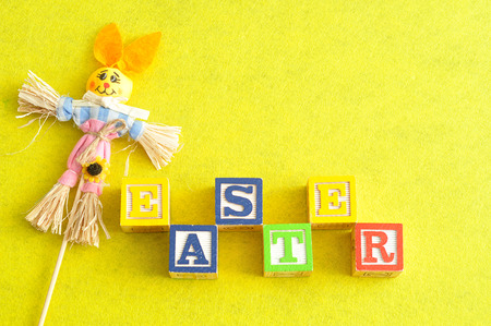 Easter spelled with alphabet blocks and a scarecrow bunny