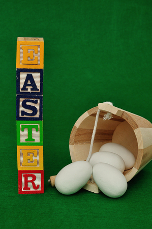 Easter spelled with alphabet blocks and a bucket of white easter eggs