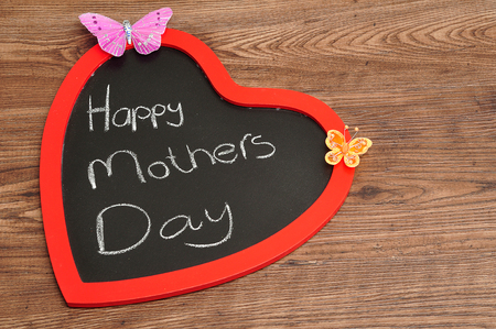 A heart shape blackboard with a happy mothers day message and two silk butterflies
