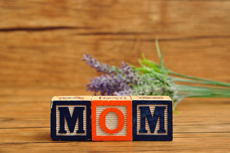 Mom spelled with colorful alphabet blocks and lavender in the background Stock Photo