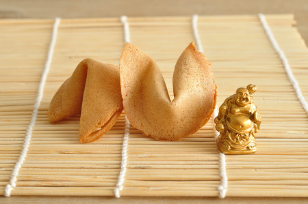 A figurine of a Buddha displayed with fortune cookies Stock Photo