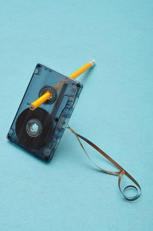 Une vieille cassette avec un crayon isolé sur un fond bleu