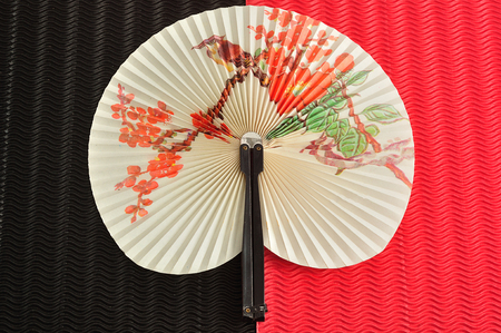 A chinese hand fan isolated on a black and red background Archivio Fotografico