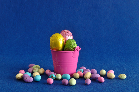 A bucket filled with easter eggs and some small ones laying next to it  Stock Photo